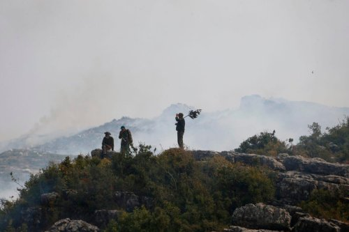 Syrian soldiers take a break as they battle a forest fire in the Ain Shams area, in the west of Hama province, on September 10, 2020 [LOUAI BESHARA/AFP via Getty Images]
