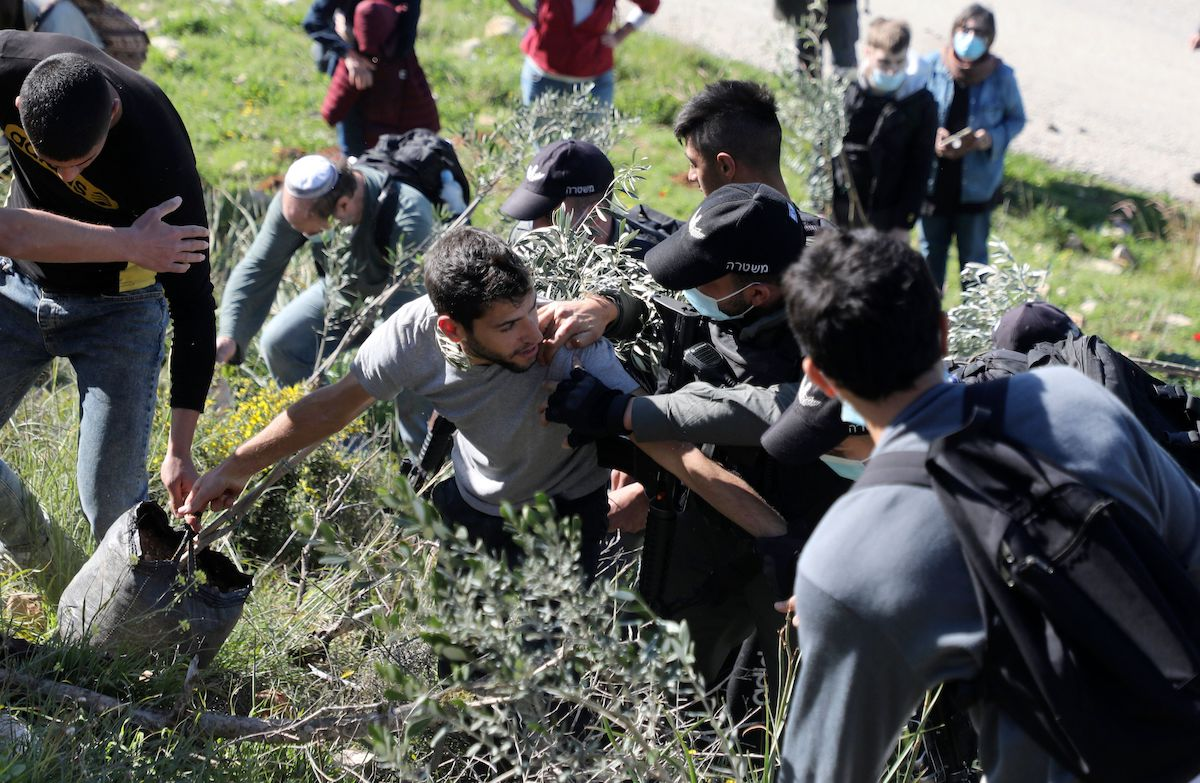 Israeli security forces prevent Israeli peace activists, international solidarity activists, and Palestinian farmers from planting olive trees in the Palestinian village of Burin near the Jewish settlement Har Brakha, south of Nablus, on 12 February 2021. [JAAFAR ASHTIYEH/AFP via Getty Images]