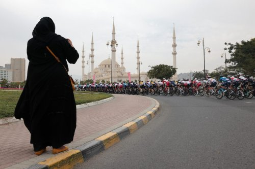 A woman takes a picture as the pack rides during the fifth stage of the UAE Cycling Tour from Fujairah Marine Club to Jebel Jais on February 25, 2021. [GIUSEPPE CACACE/AFP via Getty Images]