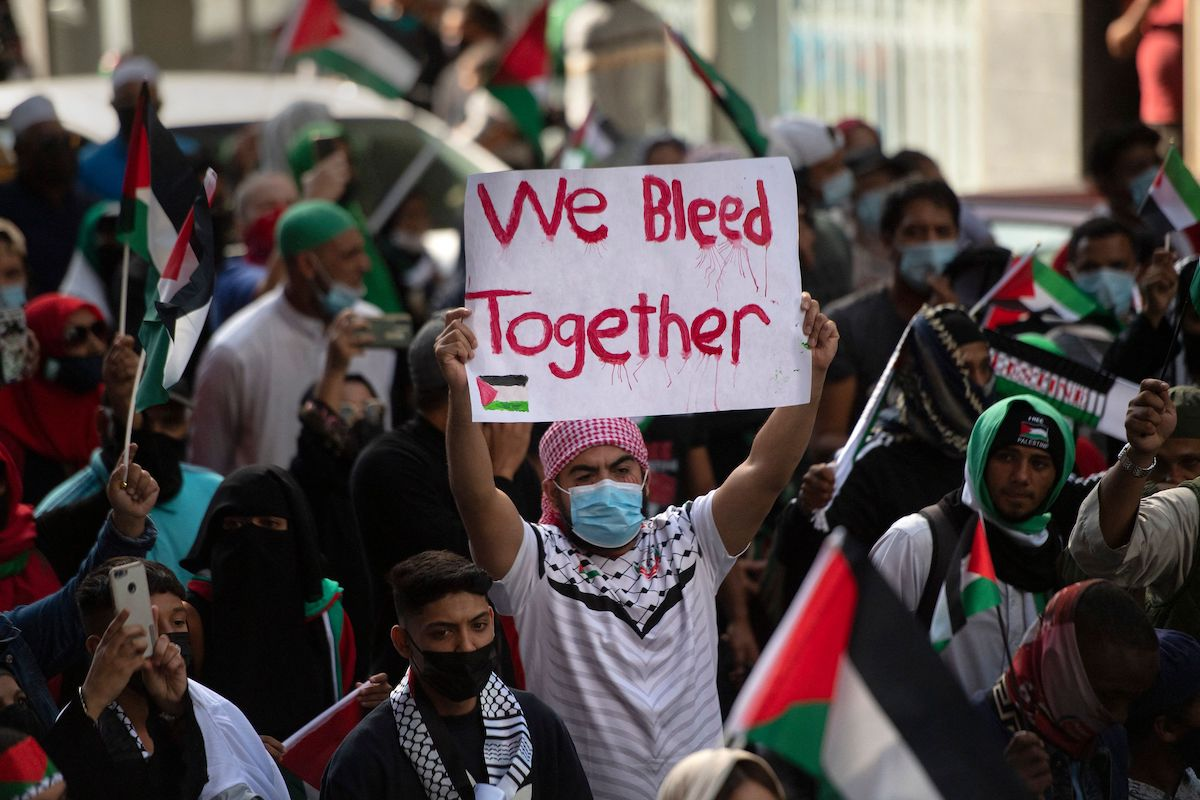 A demonstrator holds a placard as they march through the city centre in Cape Town, on 12 May 2021 during a protest against Israeli attacks on Palestinians in Gaza [RODGER BOSCH/AFP via Getty Images]