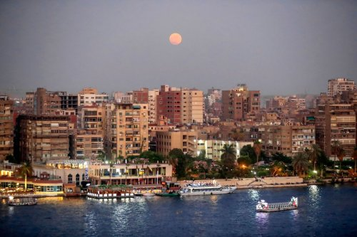 A picture taken on June 24, 2021 shows the Strawberry supermoon rising over buildings in the Egyptian capital Cairo. [KHALED DESOUKI/AFP via Getty Images]