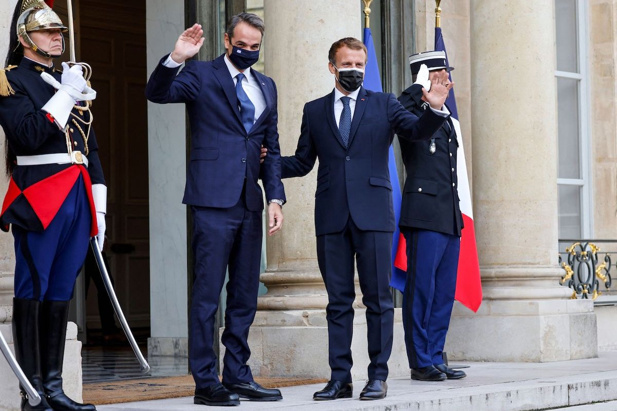 French President Emmanuel Macron (R) greets Greek Prime Minister Kyriakos Mitsotakis prior to the signing ceremony of a new defence deal at The Elysee Palace in Paris on 28 September 2021. [LUDOVIC MARIN/AFP via Getty Images]