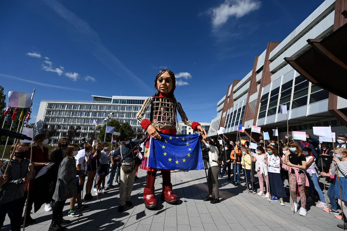 """Members of the public gather as """"Little Amal"""", a giant puppet depicting a Syrian refugee girl, arrives with a European Union flag at the Council of Europe in Strasbourg, eastern France, on 30 September 2021, as part of the initiative """"The Walk"""". [FREDERICK FLORIN/AFP via Getty Images]"""
