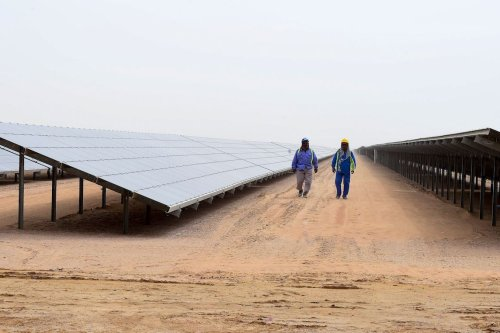 Employees walk past solar panels at the Mohammed bin Rashid Al-Maktoum Solar Park on 20 March 2017, in Dubai. [STRINGER/AFP via Getty Images]