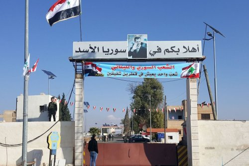 """A picture taken on December 14, 2017 shows a general view of people standing at the Al-Qaa border crossing in Lebanon and Jussiyeh in Syria. The writing in Arabic reads: """"Welcome to Assad's Syria"""". [STRINGER/AFP via Getty Images]"""