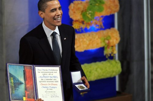 Nobel Peace Prize laureate, US President Barack Obama smiles on the podium with his diploma and gold medal during the Nobel ceremony at the City Hall in Oslo on 10 December 2009. [JEWEL SAMAD/AFP via Getty Images]