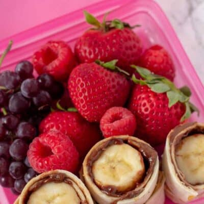 Nutella And Banana Sushi roll up in a pink lunch box container with grapes, strawberries and raspberries