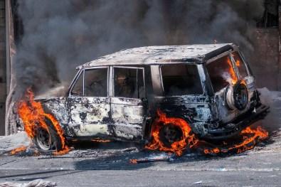 10/02 - Manifestantes incendeiam um carro durante um protesto em Porto Príncipe, Haiti / Foto: EPA