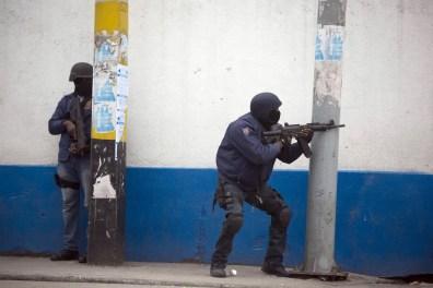 07/02 - Um policial aponta sua arma contra os manifestantes durante a manifestação para exigir a renúncia do presidente Jovenel Moise / Foto: AP