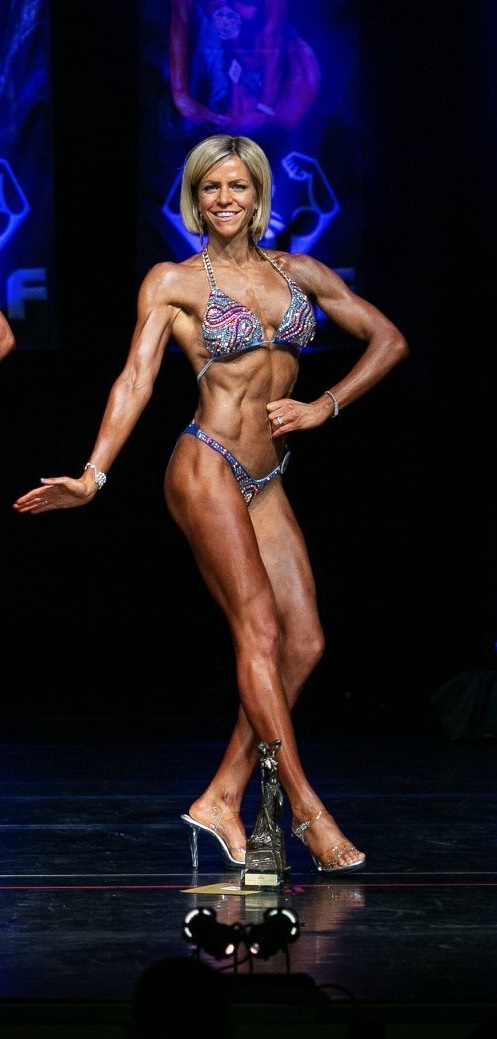 Champion Body Builder poses with one of her trophies