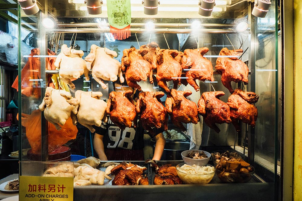 Chickens hanging in the window of a food stall, some raw and some golden brown