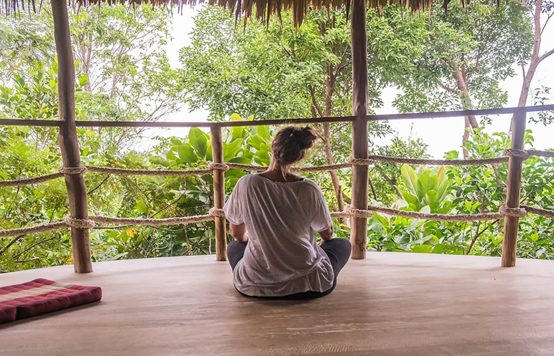 Woman sitting in lotus pose overlooking the jungle