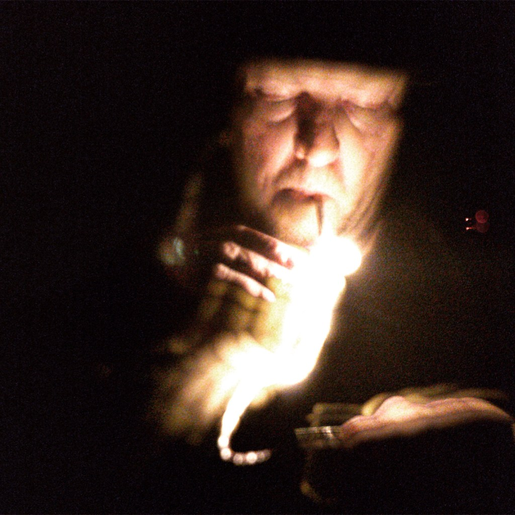Low light image of lighting a cigarette with matches, with light trails turned on during capture.