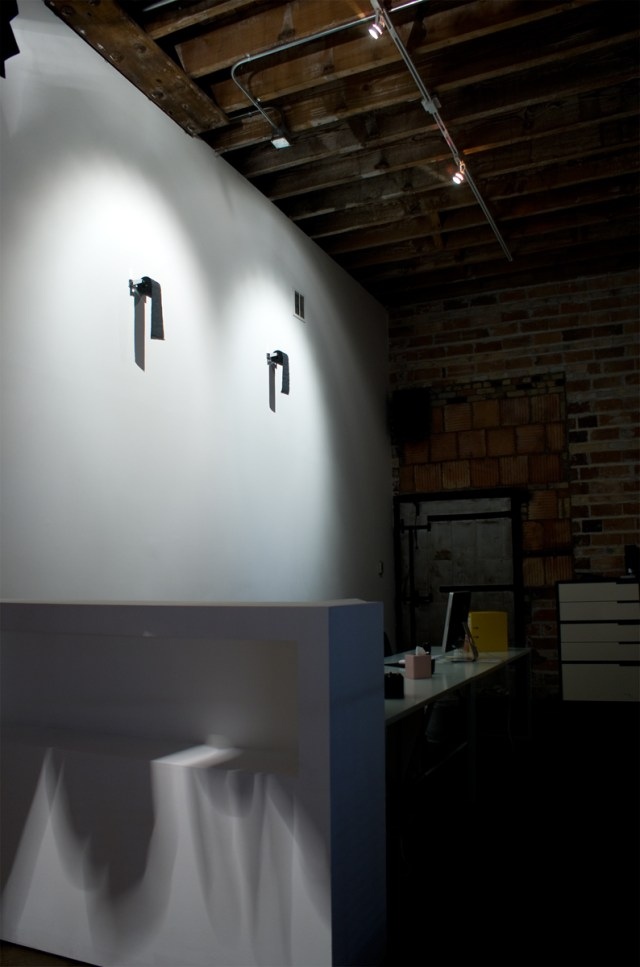 Untitled, 2009. Black toilet paper rolls, chrome toilet paper holders. Dimensions variable.