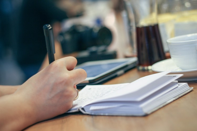 person taking notes doing business research