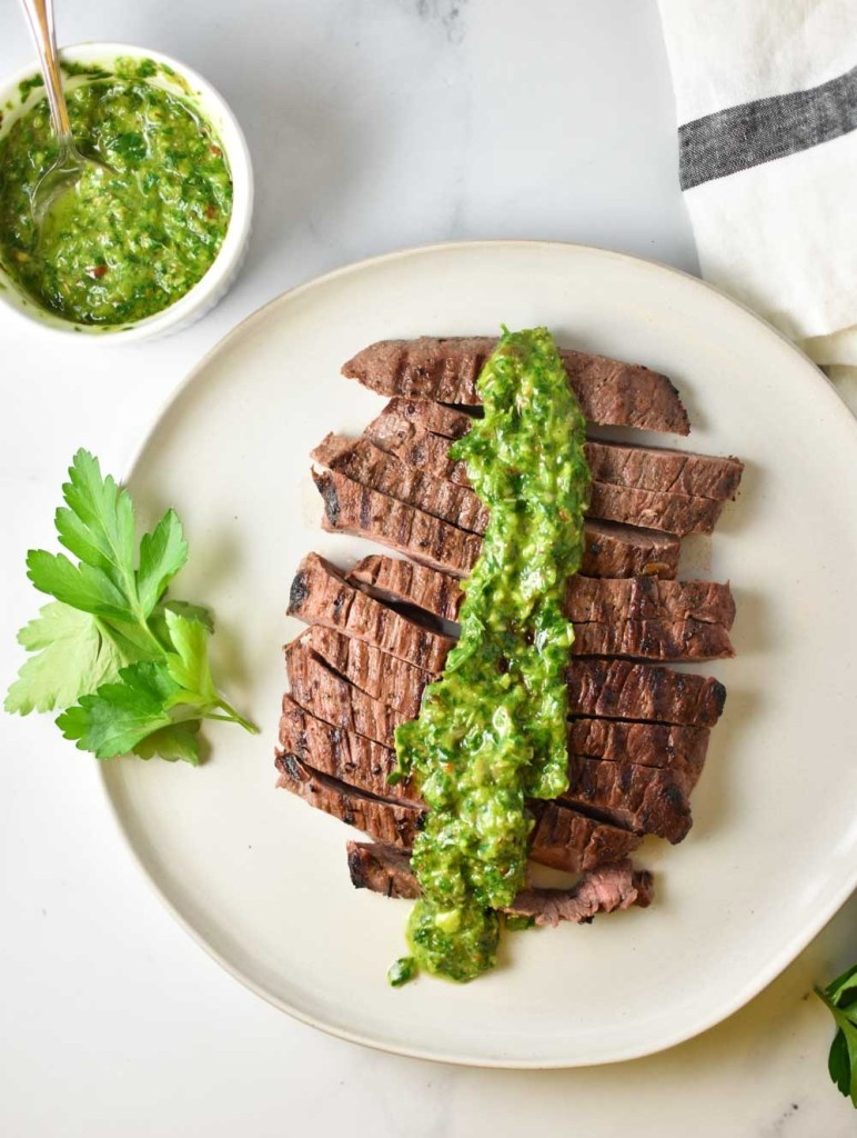 A steak on a plate with chimichurri sauce