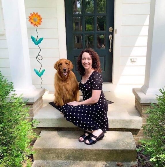 woman with curly hair and polka dot dress and dog who fought chronic migraine