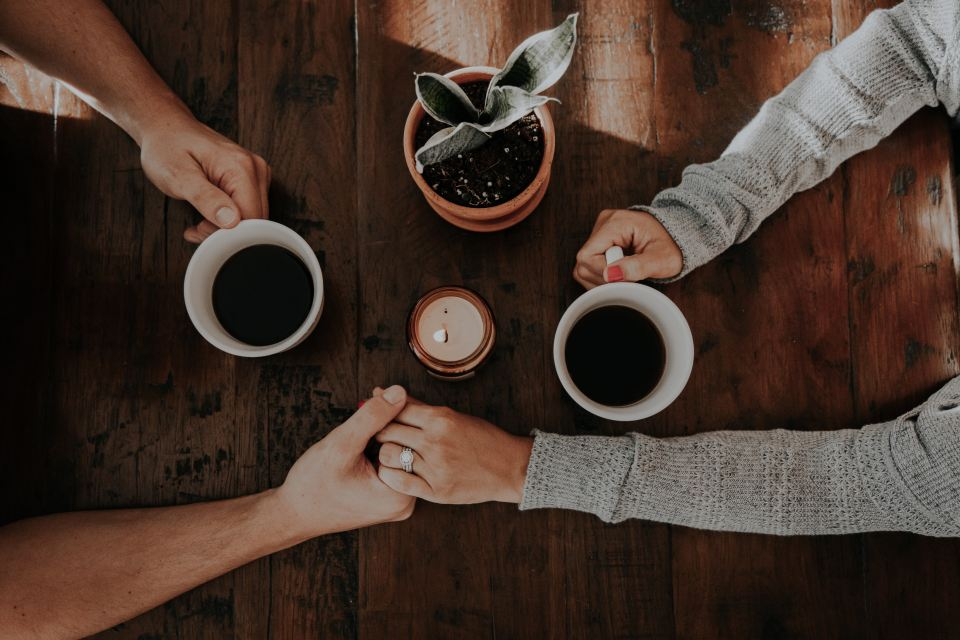 two people holding hands with coffee