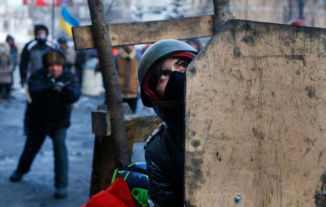 A protester shields himself during clashes with police in Kiev, Ukraine, on Jan. 23, 2014.