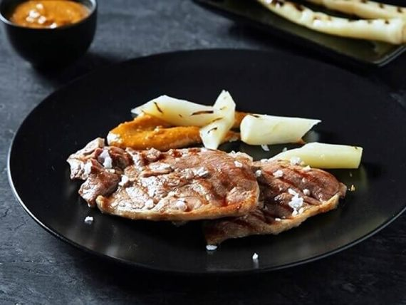 Filete de pierna de cordero aromatizada con ajos tiernos y romesco