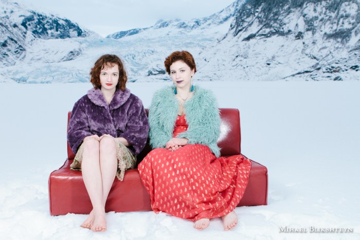 Two young women posing on a red couch in the middle of a frozen lake in front of a glacier in the winter