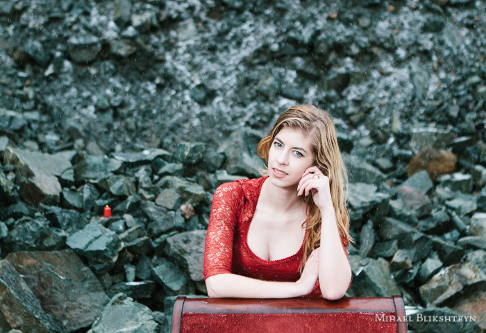 Portrait of a young woman in red dress leaning on a red velvet chair in a rock quarry with snow falling