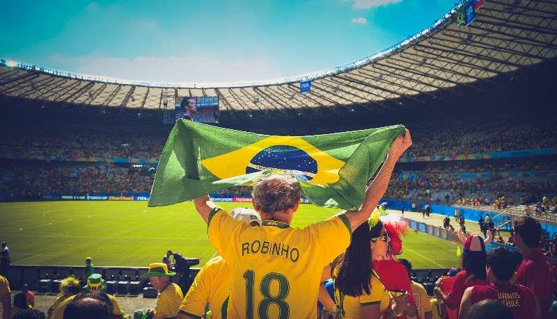 Stadion met juichende Brazilianen met een Braziliaanse vlag