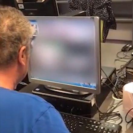 Man van middelbare leeftijd kijkt porno in een openbare bibliotheek