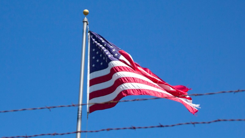 American Flag behind barbed wire