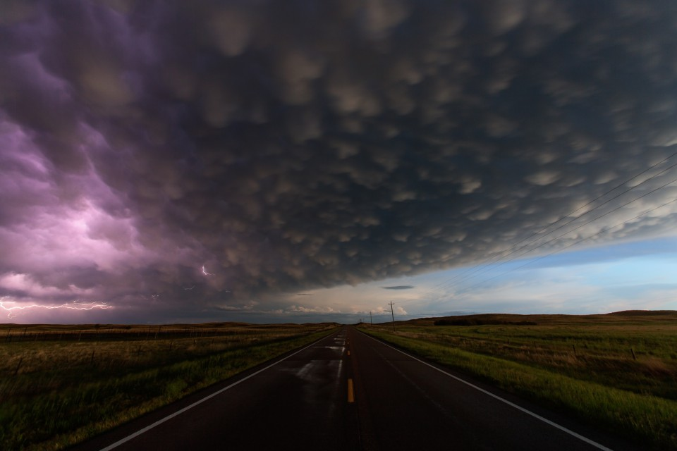 On a long, lonely highway between Marriman and Hyannis, Nebraska...a huge MCS moves by, leaving behind it wet roads and a gorgeous sky filled with mammatus clouds. A bit of lightning snakes around on the left side of the storm.