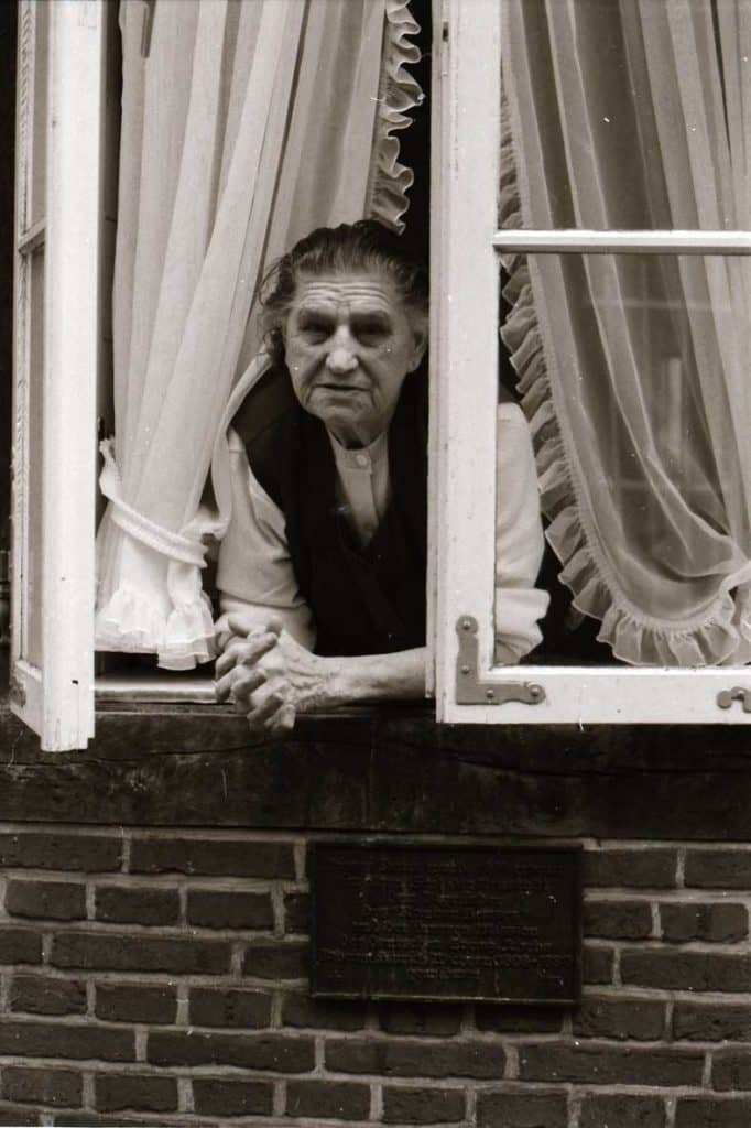 An 82 year-old leans out her window in a Hamburg street, 1984.
