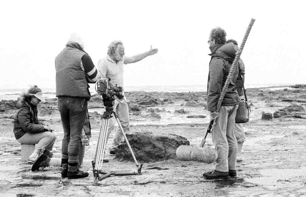 David Bellamy (arm outstretched) and his Moa's Ark crew beside the largest tree stump at the Jurassic fossil forest of Curio Bay, New Zealand (1989).