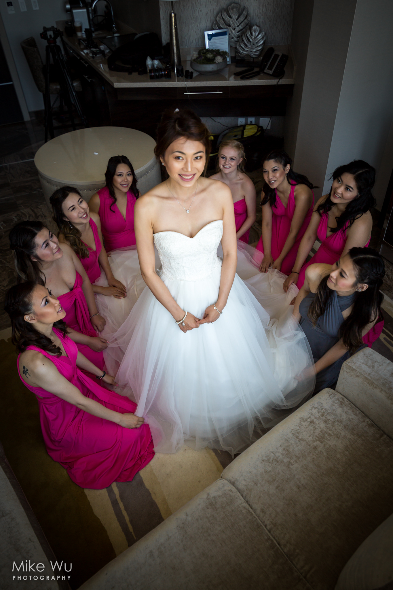 bride, smile, bridesmades, circle, huddled, love, pink, white, wedding dress, natural light, window, wedding photography, photographer, vancouver, wedding, getting ready, portrait, group