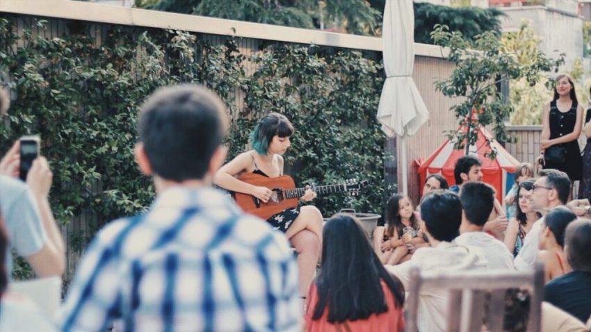 Musicista con chitarra suona su una terrazza