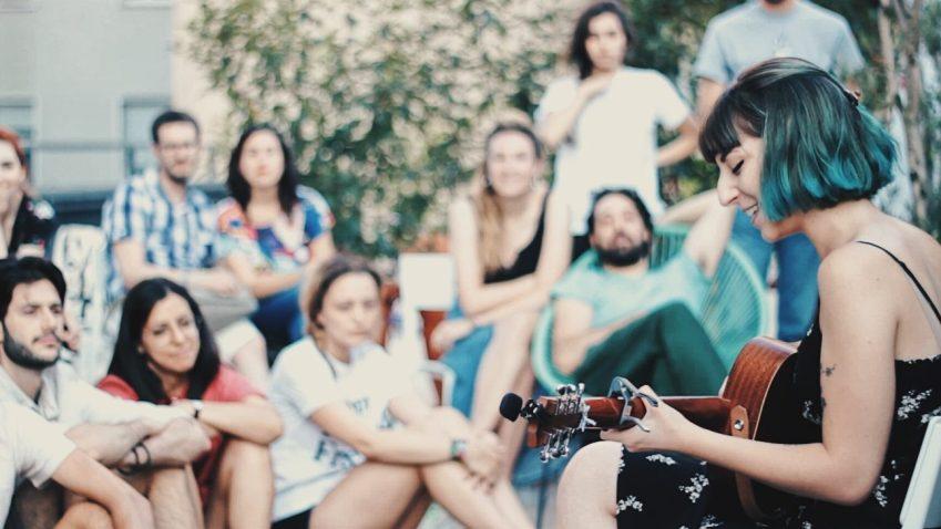 Musicista con chitarra suona davanti a un pubblico