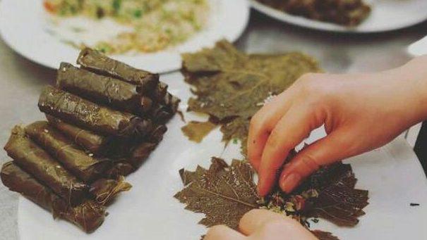 Le mani di una cuoca mentre prepara dei tipici involtini siriani