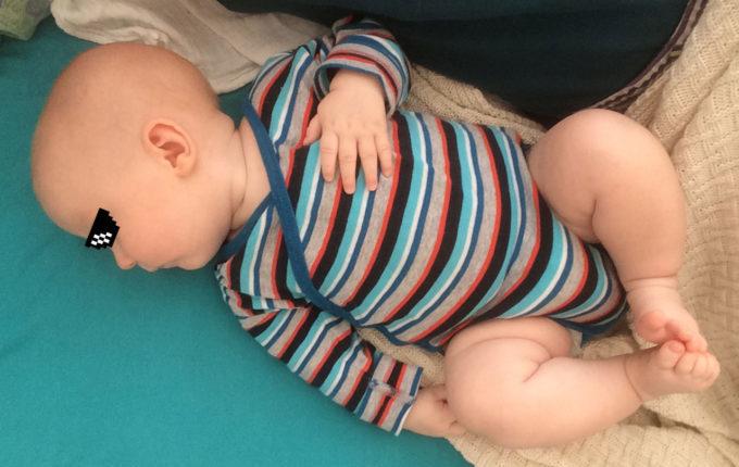 Baby mit speckigen Beinchen berührt seine Füßchen