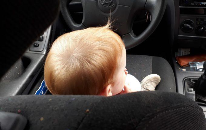 Sommertipps für Familien mit Baby und Kind - Kind sitzt vorn im Auto