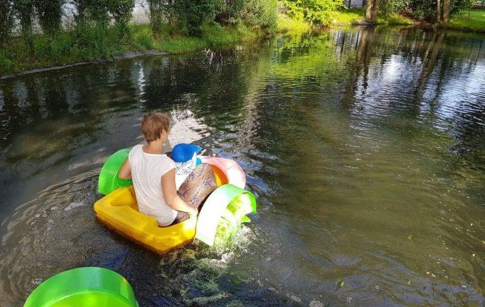 Tommys turbulente Tobewelt - Frau fährt im kleinen Boot mit Kind übers Wasser