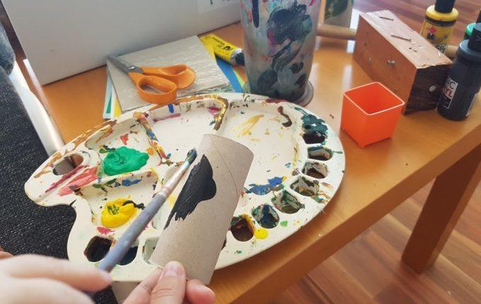 Kind malt Klopapierrolle mit Pinsel und Acrylfarbe an