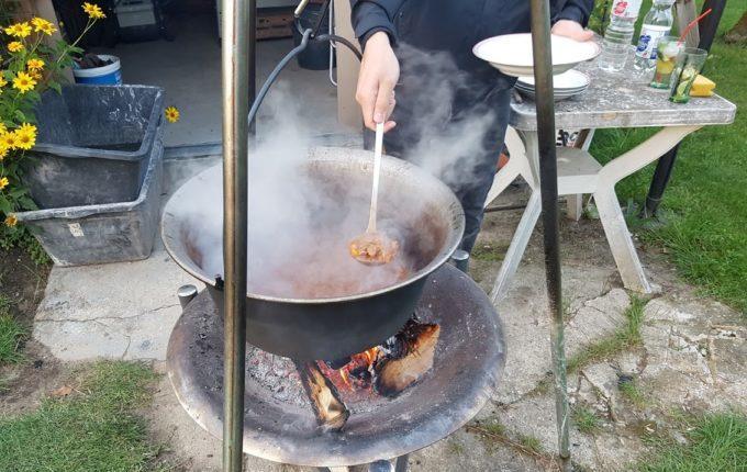 Mann füllt Kesselgulasch aus dampfendem Kessel in einen Teller