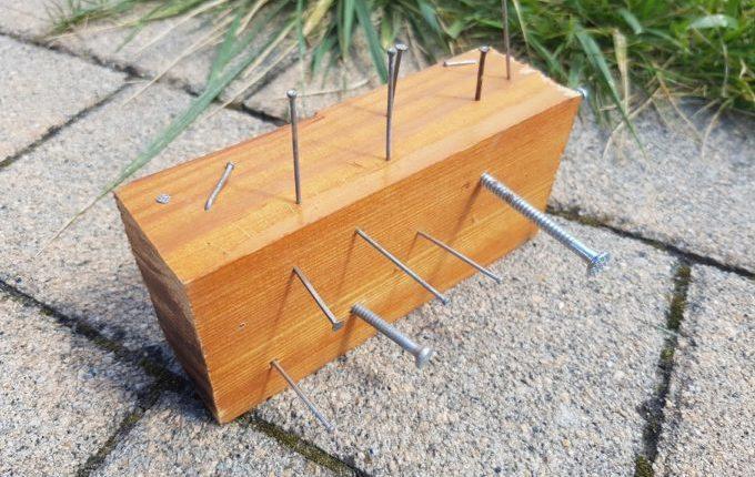 Stück Holz mit Nägeln und Nagelschrauben drin