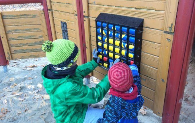 Kinder spielen im Winter auf dem Spielplatz