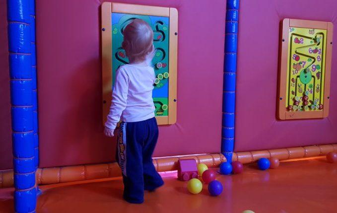 Kind spielt mit zusammen gekniffenen Beinen