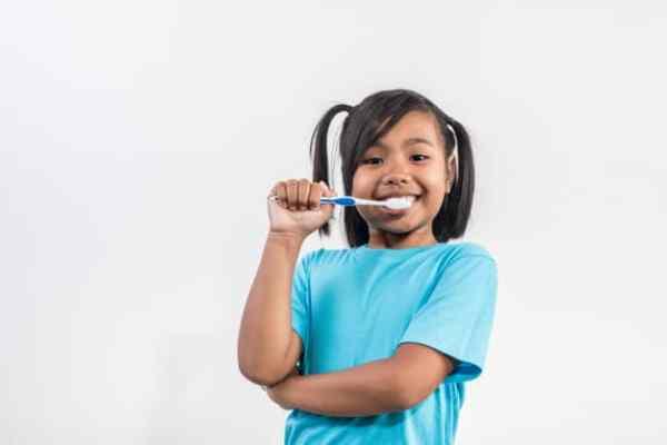 menina escovando os dentes