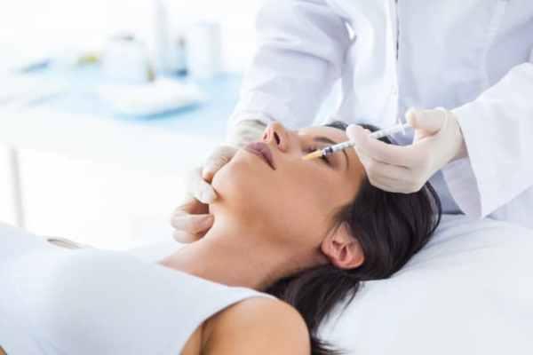 mulher aplicando botox no rosto