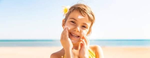 criança passando filtro solar