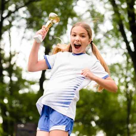 menina feliz com troféu na mão