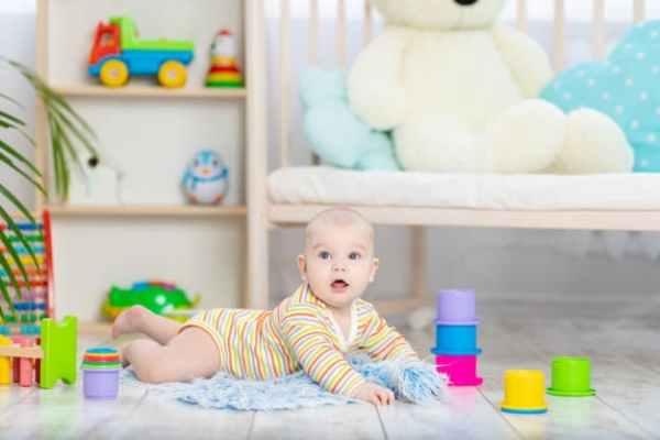 bebê deitado no chão com brinquedos