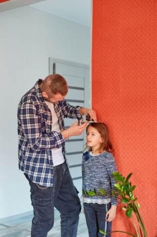 pai medindo a altura da criança